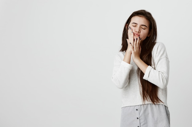 Hübsche schöne brünette teenagerfrau, die ihr langes dunkles glattes haar lose in freizeitkleidung trägt, die wangen mit den händen berührt und mit geschlossenen augen gegen graue wand posiert.