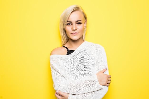 Hübsche schöne junge blonde frau im weißen pullover, der auf gelb aufwirft