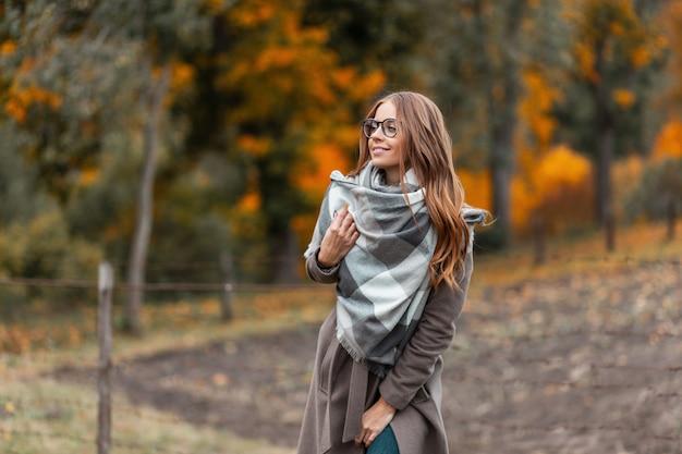 Hübsche schöne junge frau in modischer herbstoberbekleidung in stilvollen gläsern mit einem gestrickten schal genießt das entspannen außerhalb der stadt im wald. freudiges hipster-mädchen mit einem schönen lächeln im freien