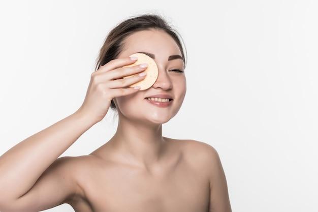 Hübsche schönheit junge asiatische frau, die ihr gesicht mit wattepad über weiß lokalisiert auf weißer wand reinigt. gesundes haut- und kosmetikkonzept.