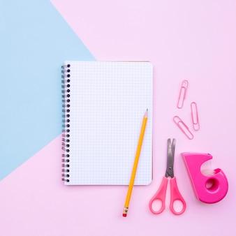 Hübsche schreibtischzusammensetzung mit notizbuch und bleistift und scheren auf hellblauem und rosa hintergrund