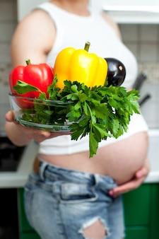 Hübsche schwangere frau, die eine platte mit gemüse und kräutern hält