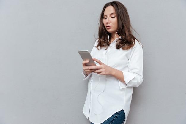 Hübsche schwangere frau mit telefon, das telefon im studio lokalisierte grauen hintergrund betrachtet