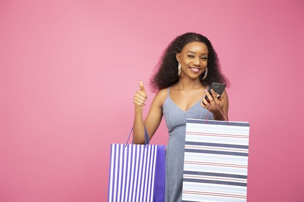 Hübsche schwarze dame, die einige einkaufstüten trägt, gibt einen daumen nach oben.