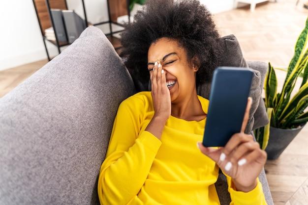 Hübsche schwarze erwachsene frau zu hause, die videos online in der social-network-app mit dem smartphone ansieht - hübsches schwarzes mädchen, das online auf dem handy arbeitet