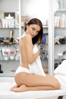 Hübsche sexy frau, die im spa sitzt und weißes höschen trägt und büste mit weißem handtuch bedeckt