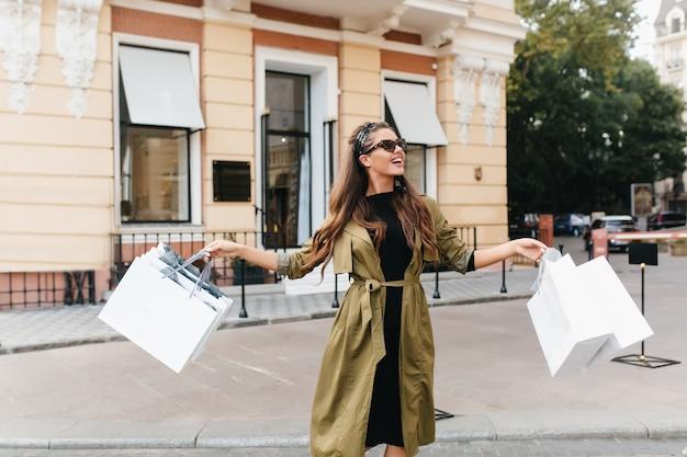 Hübsche shopaholic-frau trägt eine sonnenbrille, die taschen schwenkt und auf der straße posiert