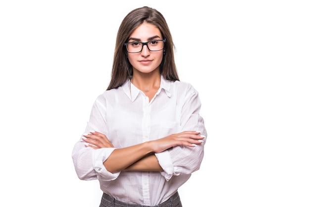 Hübsche sinnliche frau der mode in den gläsern, die auf weißer wand aufwerfen