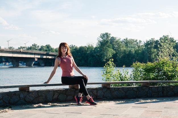 Hübsche sitzfrau im freien, park, fluss