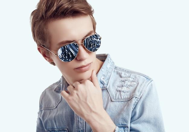 Hübsche sonnenbrille des hippie-mannes in mode, die jeansjacke trägt
