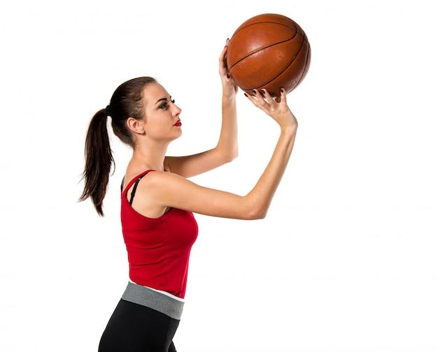 Hübsche sportfrau, die basketball spielt