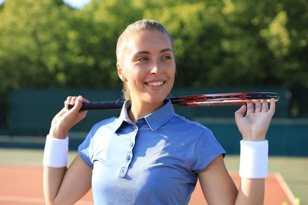 Hübsche sportlerin mit schläger am tennisplatz. gesunder lebensstil.
