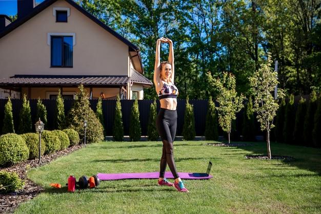 Hübsche sportliche fitnesstrainerin wärmen sich vor dem online-training im garten auf