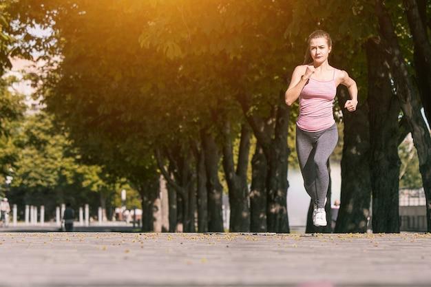 Hübsche sportliche frau, die am park im sonnenaufganglicht joggt