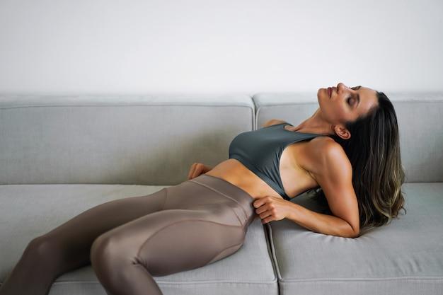 Hübsche sportliche frau, die auf beigem sofa posiert