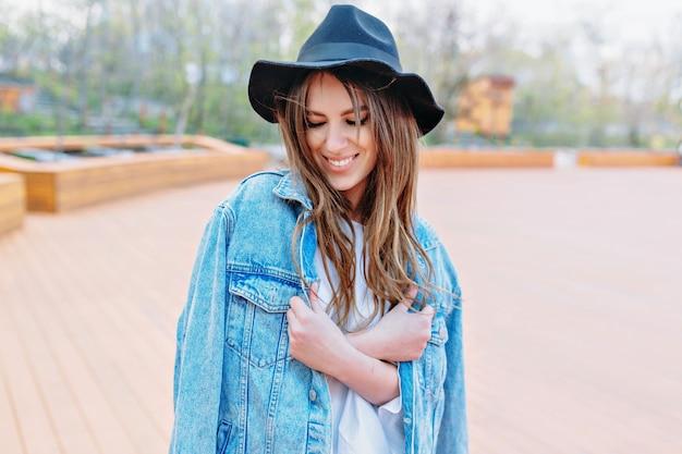 Hübsche stilfrau mit langen dunklen haaren, die schwarzen hut und jeansjacke tragen, schließt ihre augen mit herrlichem lächeln. sommerstimmung. außenporträt im park