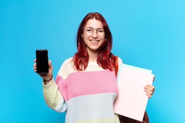 Hübsche studentin, die ihren zellenbildschirm zeigt