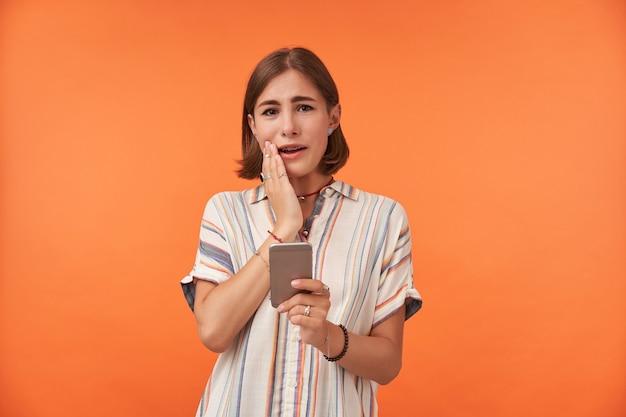 Hübsche studentin mit brünetten haaren, hosenträgern, gestreiftem hemd und ringen. berühren sie ihren mundwinkel und halten sie ein smartphone.