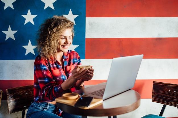Hübsche studentin mit süßem lächeln, die etwas auf dem netbook tastet, während sie sich nach den vorlesungen an der universität entspannt?