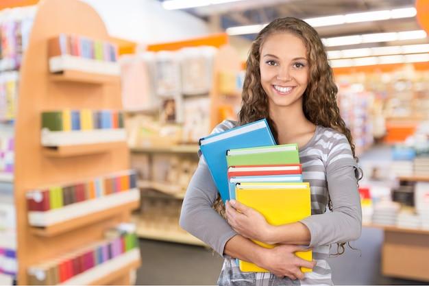Hübsche studentin umgeben von bibliotheksbüchern