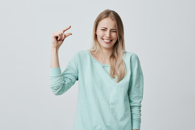 Hübsche süße blonde frau in freizeitkleidung, die etwas kleines mit den händen beim gestikulieren zeigt und breit mit den zähnen lächelt. blonde europäische frau, die größe der kleinen schachtel demonstriert