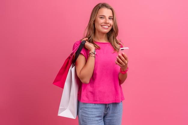 Hübsche süße lächelnde frau in rosa hemd lächelnd posiert auf rosa mit smartphone mit einkaufstüten