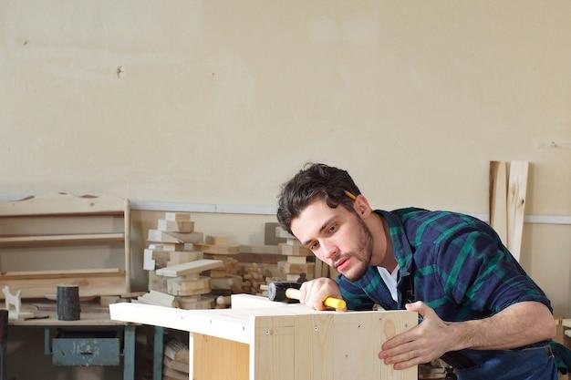 Hübsche tischlerarbeit in der zimmerei. er ist ein erfolgreicher unternehmer an seinem arbeitsplatz.