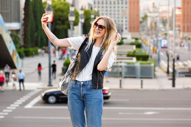 Hübsche touristische blonde frau, die selfie auf der straße macht