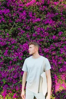 Hübsche tragende stofftasche des jungen mannes, die nahe rosa blumenbaum steht