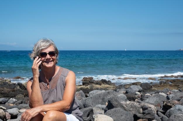Hübsche und fröhliche ältere frau mit grauem haar, die auf den felsen des strandes sitzt. mit dem handy sprechen und lächeln. gelassenheit und entspannung. blauer hintergrund von meer und himmel