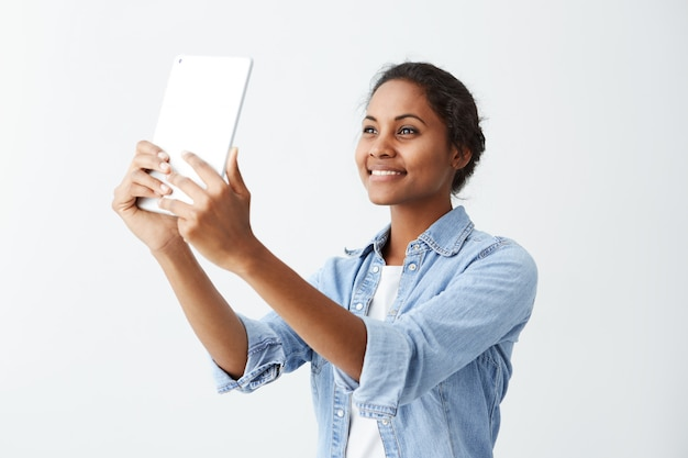 Hübsche und fröhliche afroamerikanische junge frau im blauen hemd über weißem t-shirt, das für selfie aufwirft und lächelt, tablette auf weißer wand hält menschen, emotionen und moderne technologien