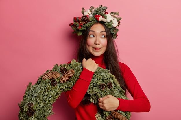 Hübsche und junge frau, die weihnachtskranz auf ihrem kopf trägt