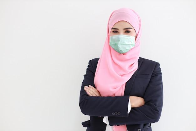 Hübsche und selbstbewusste muslimische junge asiatische frau, die blauen anzug mit medizinischer schützender gesichtsmaske trägt, um infektion von coronavirus im studio auf lokalisiertem weißem hintergrundporträt zu schützen