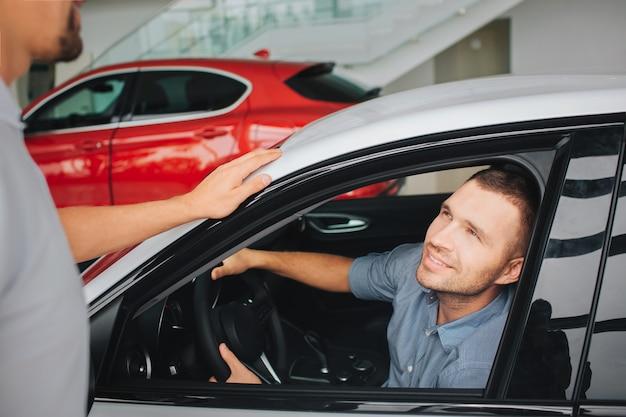 Hübsche und zufriedene junge männer, die im weißen auto sitzen und manager betrachten. er lächelt. guy hält hände am lenkrad. der bärtige manager steht neben dem weißen auto und schaut den kunden an.
