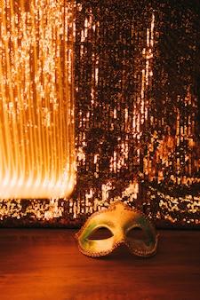 Hübsche venetianische goldene karnevalsmaske mit schönem goldenem funkelnhintergrund