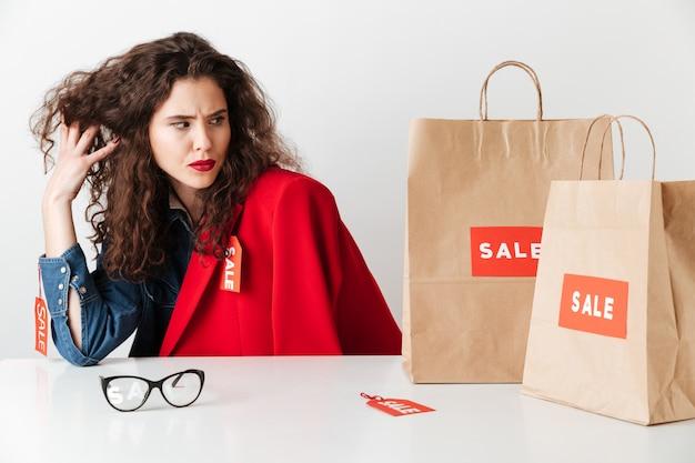 Hübsche verkaufsfrau, die papiereinkaufstaschen sitzt und betrachtet