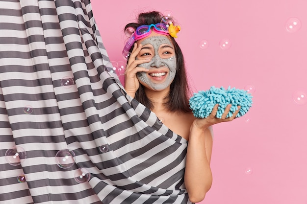 Hübsche verträumte asiatin nimmt morgens duschen zu hause trägt schönheitsgesichtsmaske auf, wäscht körper mit schwamm und reinigt die haut genießt erfrischende hygieneverfahren