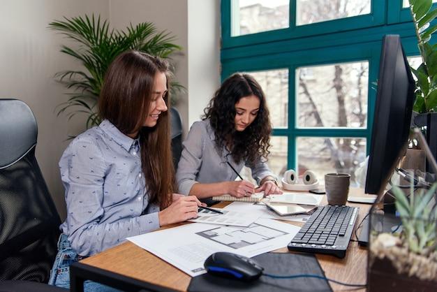 Hübsche weibliche architekten in blauen hemden, die mit farbpalette arbeiten, um design und farben im büro zu wählen.