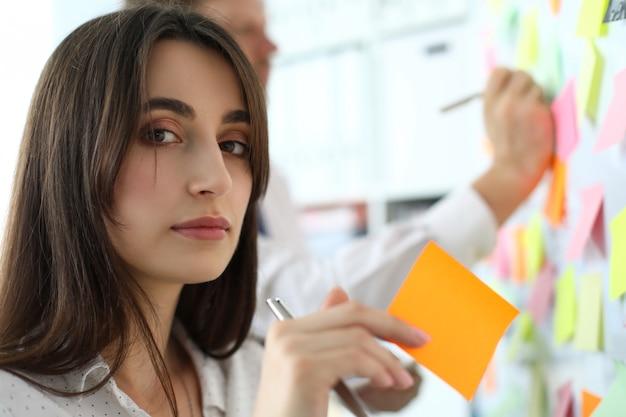 Hübsche weibliche büroangestellte, die klebriges papier hält