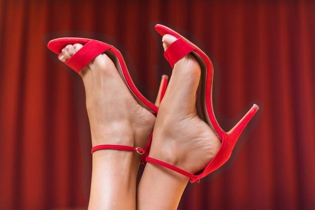 Hübsche weibliche füße in roten sandalen mit hohem absatz