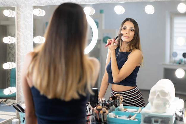 Hübsche weibliche kosmetikerin, die im schönheitssalon steht
