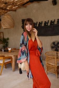 Hübsche weiße frau im stilvollen sommer-bohemain-autfit, das im tropischen café aufwirft.