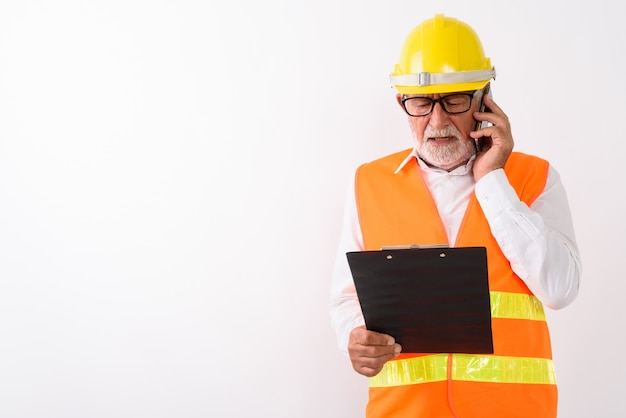 Hübscher älterer bärtiger bauarbeiter, der auf zwischenablage liest, während er brillen trägt und auf handy auf weiß spricht