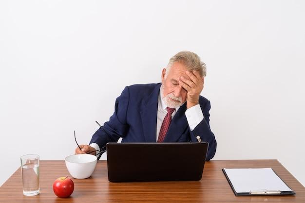 Hübscher älterer bärtiger geschäftsmann, der brillen hält, während er kopfschmerzen mit laptop und grundlegenden dingen für die arbeit am holztisch auf weiß hat
