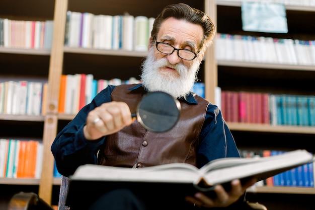 Hübscher älterer bärtiger mann, bibliothekar oder professor, in der bibliothek, sitzend auf dem hintergrund von bücherschränken, hält lupe und lesebuch