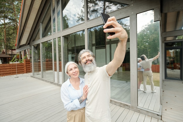 Hübscher älterer bärtiger mann, der frau umarmt, während er selfie mit ihm nahe glashaus nimmt