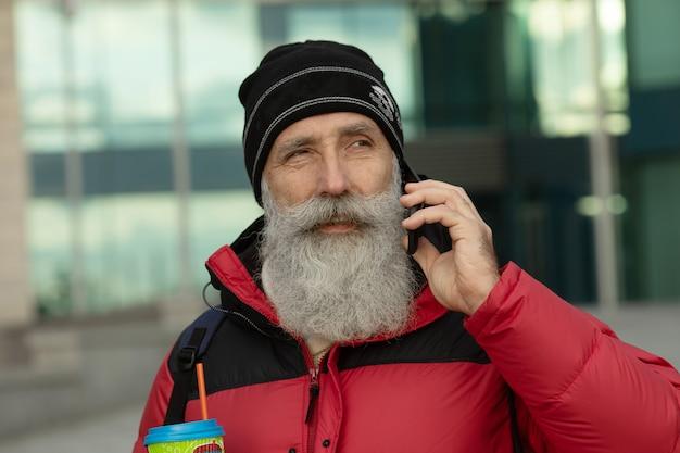 Hübscher älterer bärtiger mann spricht durch ein smartphone, während er kaffeepause auf einer straße neben bürogebäude hat.