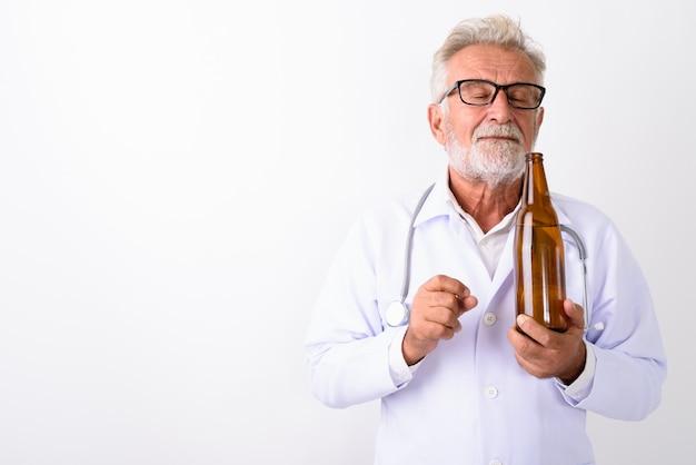 Hübscher älterer bärtiger mannarzt, der flasche bier mit geschlossenen augen auf weiß riecht
