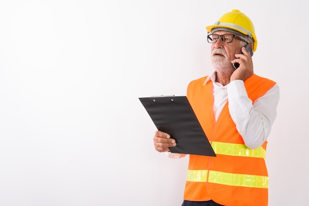 Hübscher älterer bärtiger mannbauarbeiter, der denkt, während er zwischenablage hält und auf handy mit brille auf weiß spricht