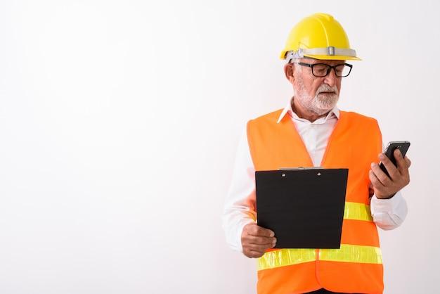 Hübscher älterer bärtiger mannbauarbeiter, der handy verwendet, während zwischenablage hält und brillen auf weiß trägt